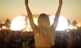young woman in front of crowd on woodstock style rock concert waving hand to music.